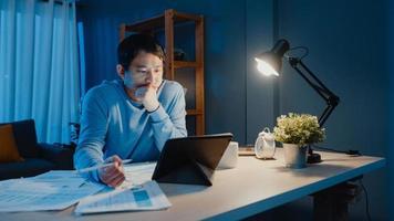 Asien frilans affärsman fokus arbete penna skriva på surfplatta upptagen med full av grafpapper på skrivbordet i vardagsrummet hemma övertid på natten, arbeta hemifrån under covid-19-pandemikonceptet. foto