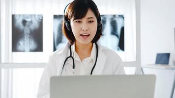 ung asiatisk kvinnlig läkare i vit medicinsk uniform med stetoskop som använder dator bärbar dator talar videokonferenssamtal med patienten vid skrivbordet på vårdkliniken eller sjukhuset. konsult- och terapikoncept foto
