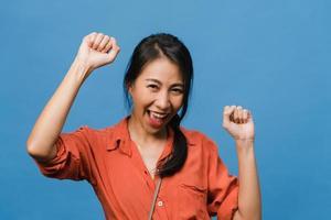 ung asiatisk dam med positivt uttryck, glad och spännande, klädd i vardagsduk och titta på kameran över blå bakgrund. glad förtjusande glad kvinna jublar över framgång. ansiktsuttryck koncept. foto
