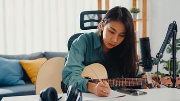 glad asien kvinna låtskrivare spela akustisk gitarr lyssna låt från smartphone tänka och skriva anteckningar texter sång i papper sitta i vardagsrummet hemma studio. musikproduktion hemma koncept. foto