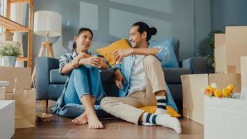 lyckliga asiatiska unga attraktiva par man och kvinna sitter vid nytt hem dricka kaffe koppla av och prata leende med kartongförpackning förvaring för att flytta i nytt hus. unga gifta asiatiska flytta hem koncept. foto