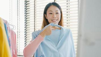 vacker attraktiv asiatisk dam som väljer kläder på klädhängare som ser sig själv i spegeln i sovrummet hemma. tjej tänk vad man ska ha på sig en casual skjorta. livsstil kvinnor slappna av hemma koncept. foto