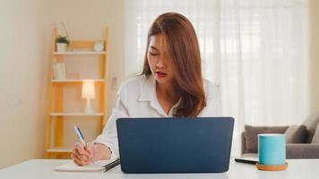 porträtt av frilansande asiatiska kvinnor casual wear med bärbar dator som arbetar i vardagsrummet hemma. arbeta hemifrån, arbeta på distans, självisolering, social distansering, karantän för förebyggande av coronavirus. foto