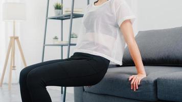 ung koreansk dam i sportkläder övningar som tränar och gör tricep dips lutade på soffan i vardagsrummet hemma. social distans, isolering under viruset. övningar för underkroppen. foto