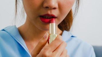 ung asiatisk kvinna som använder läppstift make up i spegeln, glad kvinna som använder skönhetskosmetik för att förbättra sig redo att arbeta i sovrummet hemma. livsstil kvinnor hemma koncept. foto