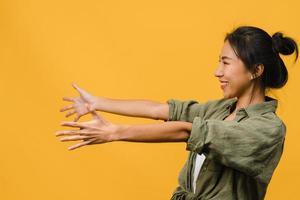 porträtt av ung asiatisk dam med positivt uttryck, le brett, klädd i vardagskläder över gul bakgrund. glad förtjusande glad kvinna jublar över framgång. ansiktsuttryck koncept. foto