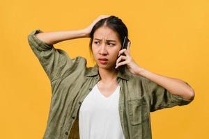 ung asiatisk dam pratar i telefon med negativt uttryck, upphetsad skrik, gråter känslomässigt arg i avslappnad trasa och står isolerad på gul bakgrund med tomt kopieringsutrymme. ansiktsuttryck koncept. foto