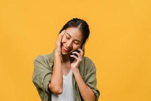 ung asiatisk dam pratar i telefon med positivt uttryck, ler brett, klädd i vardagskläder som känner lycka och står isolerad på gul bakgrund. glad förtjusande glad kvinna jublar över framgång. foto