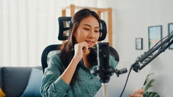 attraktiv asien tjej spela in podcast använda mikrofon håll papper skapa innehåll för ljud blogg prata och öva för granskning ämne i hennes rum. göra ljudpodd hemifrån, ljudutrustningskoncept. foto