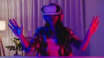 asien dam bär vr spel headset ha kul upplevelse bärbar virtuell förstärkt ar verklighet digital innovation teknik lyckligt ögonblick nyår neon natt fest händelse firande i vardagsrummet hemma foto