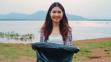 porträtt av unga asiatiska damfrivilliga hjälper till att hålla naturen ren och titta på kameran och le med svarta sopsäckar på stranden. koncept om miljöskyddsföroreningar. foto