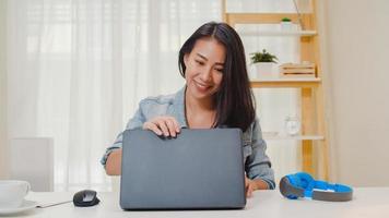 porträtt av frilans smarta affärskvinnor casual wear med bärbar dator som arbetar på arbetsplatsen i vardagsrummet hemma. glad ung asiatisk tjej koppla av sittande på skrivbordssökning och göra jobb på internet. foto
