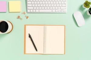 kreativt plattläggningsfoto av skrivbordet på arbetsytan. ovanifrån kontorsbord med tangentbord, mus och öppen mockup svart anteckningsbok på pastellgrön färgbakgrund. ovanifrån håna med kopia utrymme fotografering. foto