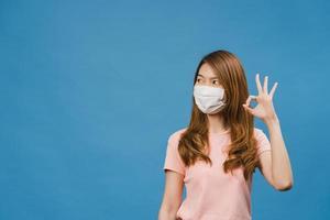 ung asiatisk tjej bär medicinsk ansiktsmask gestikulerar skylt med klädd i vardaglig trasa och titta på kameran isolerad på blå bakgrund. självisolering, social distansering, karantän för corona-virus. foto