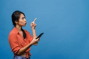 porträtt av ung asiatisk dam med mobiltelefon med glada uttryck, visa något fantastiskt på tomt utrymme i vardagskläder och stå isolerat över blå bakgrund. ansiktsuttryck koncept. foto