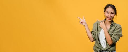 ung asiatisk dam som ler med glatt uttryck, visar något fantastiskt på tomt utrymme i avslappnad trasa och tittar på kameran isolerad över gul bakgrund. panoramabanner med kopieringsutrymme. foto