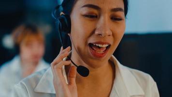 närbild av asiatiska unga call center team eller kundsupport chef med hjälp av dator och mikrofon headset arbetar teknisk support i sen natt kontor. telemarketing eller försäljningsjobb koncept. foto