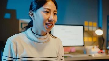 glada unga asiatiska affärsmän och affärskvinnor möter brainstorming några nya idéer om projekt till sin partner som arbetar tillsammans planerar framgångsstrategi njuter av lagarbete i små moderna nattkontor. foto