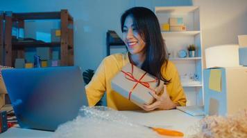 ung asiatisk affärskvinna använder smartphone ta emot inköpsorder och visa produktförpackningar till klientvideo live streaming online i butik på natten. småföretagare, online marknadsföringskoncept. foto
