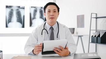 ung asiatisk manlig läkare i vit medicinsk uniform med stetoskop med dator bärbar dator samtal videosamtal med patienten, tittar på kameran på sjukhus. konsult- och terapikoncept. foto