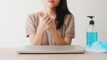 asiatisk kvinna som använder alkoholgel handsprit tvättar handen innan den öppna bärbara datorn för att skydda coronaviruset. kvinnor pressar alkohol för att städa för hygien när social distans stannar hemma och självkarantän foto