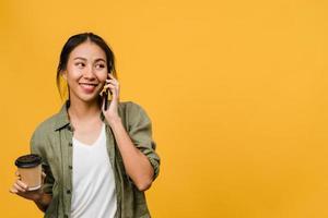 ung asiatisk dam pratar i telefon och håller kaffekoppen med positivt uttryck, ler brett, klädd i avslappnad trasa som känner lycka och står isolerad på gul bakgrund. ansiktsuttryck koncept. foto