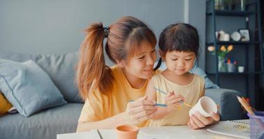 glad glad asien familj familj mamma lära småbarn flicka måla keramik kruka ha kul koppla av på bordet i vardagsrummet hemma. umgås tillsammans, social distans, karantän för förebyggande av coronavirus. foto