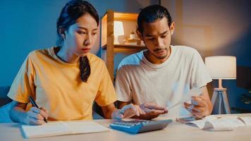 stress asien par man och kvinna använder miniräknare för att beräkna familjens budget, skulder, utgifter under den finansiella ekonomiska krisen hemma på natten. äktenskap pengar problem, familj budget plan koncept. foto
