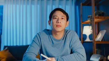 Asien affärsman tittar på kamerafokus online videosamtal möte uppdrag arbete med kollega på surfplatta i vardagsrummet hemma övertid på natten, arbete hemifrån coronavirus pandemi koncept. foto