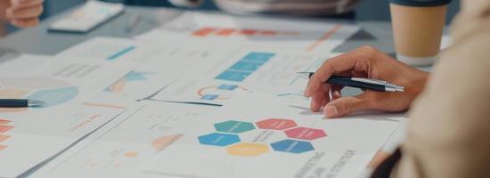unga asiatiska affärsmän möter brainstorming några nya idéer om projekt till partner som arbetar tillsammans planerar framgångsstrategi njuter av lagarbete på kontoret. panoramabannerbakgrund med kopieringsutrymme. foto