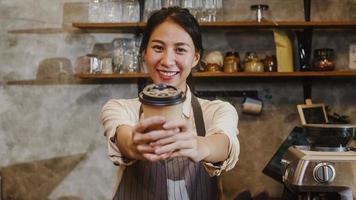 porträtt ung asiatisk dam barista servitris som håller kaffe kopp känner sig lycklig på urbana café. Asien småföretagare flicka i förkläde koppla av tandiga leende ser till kamerastativ vid räknaren i kafé. foto