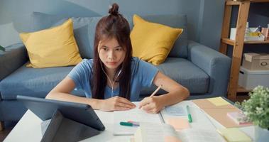 ung asiatisk tjej tonåring med fritidsdräkt hörlurar använda digital surfplatta lära sig online skriva föreläsning anteckningsbok i vardagsrummet hemma. isolera utbildning online e-learning coronavirus-pandemikoncept. foto