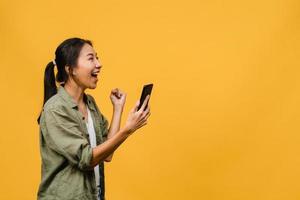 förvånad ung asiatisk dam med mobiltelefon med positivt uttryck, ler brett, klädd i vardagskläder och står isolerad på gul bakgrund. glad förtjusande glad kvinna jublar över framgång. foto
