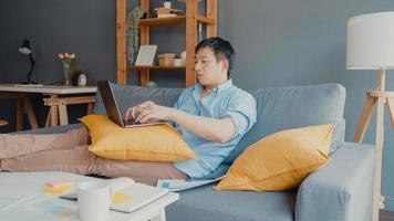 frilans asien kille fritidskläder med bärbar dator online -lärande i vardagsrummet hemma. arbeta hemifrån, arbeta på distans, distansutbildning, social distansering, karantän för förebyggande av corona -virus. foto