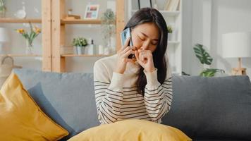 sjuk ung asiatisk kvinna hålla medicin sitta i soffan använda smartphone samtal för att rådgöra med läkare hemma. tjej tar medicin efter läkarorder, karantän hemma, socialt distanserat coronavirus -koncept. foto