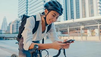 le asiatisk affärskvinna med ryggsäck använda smart telefon titta kamera i stad stå på gatan med cykel gå till jobbet på kontoret. sportflicka använder telefonen för arbete. pendla till jobbet, affärspendlare i staden. foto