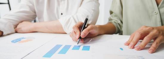 unga asiatiska affärsmän möter brainstorming idéer om nya pappersarbete projektkollegor arbetar tillsammans planerar framgångsstrategi njuter av lagarbete på kontoret. panoramabannerbakgrund med kopieringsutrymme. foto
