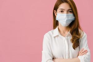ung asiatisk tjej bär medicinsk ansiktsmask med armarna i kors, klädd i vardagsduk och tittar på kameran isolerad på blå bakgrund. självisolering, social distansering, karantän för corona-virus. foto