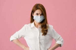 ung asiatisk tjej bär medicinsk ansiktsmask med negativt uttryck, upphetsat skrik, gråter emotionellt arg och tittar på kameran isolerad på rosa bakgrund. social distansering, karantän för corona. foto