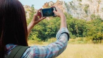 glad ung resenär asiatisk dam med ryggsäck med smartphone för att ta en bild vid fjällsjön. koreansk tjej njut av semester äventyr känner glad frihet. livsstilsresor och koppla av koncept. foto