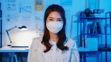 porträtt av den vackra verkställande affärskvinnan som bär medicinsk ansiktsmask som tittar på kameran och ler i modern kontorsarbetsplats natt. ung asiatisk dam prata med kollega i videosamtalsmöte hemma. foto
