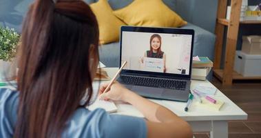 ung asiatisk tjej med tillfällig användning dator bärbar videosamtal lära online med lärare skriva föreläsning anteckningsbok vardagsrum hemma. isolera utbildning online e-learning coronavirus-pandemikoncept. foto