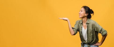 porträtt av ung asiatisk dam som ler med glatt uttryck, visar något fantastiskt på tomt utrymme i vardagskläder och står isolerat över gul bakgrund. panoramabanner med kopieringsutrymme. foto