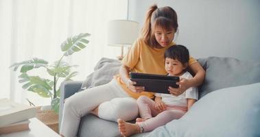 glad glad asiatisk familj familj mamma och söt unge med digital tablett intresse tecknad film och titta på film ha kul koppla av på soffan i vardagsrummet hemma. spendera tid tillsammans, karantän för coronavirus. foto