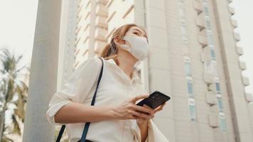 ung asiatisk affärskvinna i mode kontorkläder som bär medicinsk ansiktsmask som kommer på vägen och tar taxi och använder smart telefon medan du står utomhus i den urbana moderna staden. business on the go -koncept. foto