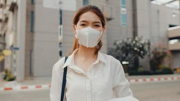 framgångsrik ung asiatisk affärskvinna i mode kontorkläder bär medicinsk ansiktsmask leende och tittar på kameran medan han är glad att stå ensam utomhus i modern modern stad. business on the go -koncept. foto
