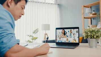 ung asiatisk affärsman som använder bärbar dator pratar med kollegor om planering i videosamtalsmöte medan han arbetar hemifrån i vardagsrummet. självisolering, social distansering, karantän för förebyggande av corona-virus. foto