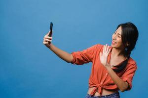 leende bedårande asiatisk kvinna som gör selfie -foto på smart telefon med positivt uttryck i vardagskläder och stativ isolerad på blå bakgrund. glad förtjusande glad kvinna jublar över framgång. foto