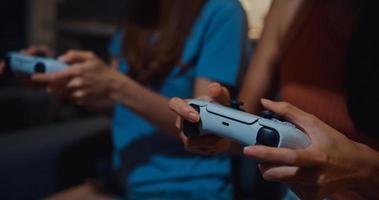 närbild fokus asien par damer hand njuta av lyckligt ögonblick använda controller gamepad spela videospel webbplats på soffan vardagsrum i hemmet vid mörk natt. helgaktivitet karantän koncept. foto