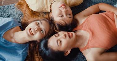 ovanifrån närbild grupp asien härliga damer med avslappnad ha kul lycka ögonblick njuta av prat och skvaller konversation på mattan i golvet vardagsrummet hemma. livsstilsaktivitet karantän koncept. foto